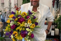 Maxim Averin with a colorful bouquet of Solidago, delphinium, eustoma, Helianthus, Campanula and tlaspi.